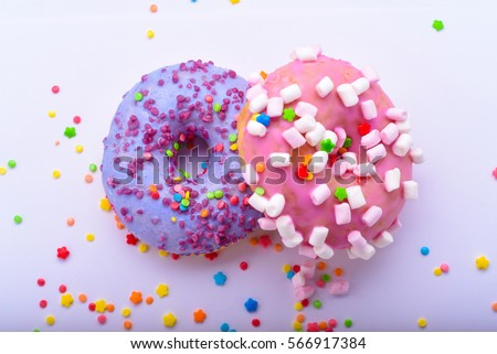 Purple donut with chocolate sprinkles and pink donut with marshmallows on a light background with colored sprinkles #566917384
