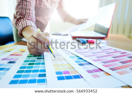 Graphic design and color swatches and pens on a desk. Architectural drawing with work tools and accessories. #566933452