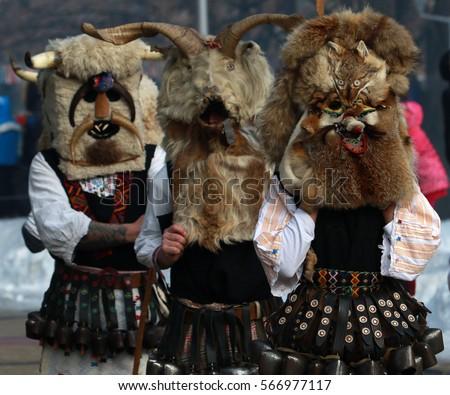 PERNIK, BULGARIA - JANUARY 29, 2017 - Masquerade festival Surva in Pernik, Bulgaria. People with mask called Kukeri dance and perform to scare the evil spirits.  #566977117