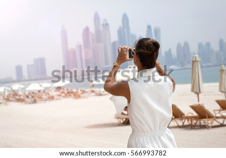 Woman taking phone picture of Dubai skylines. Female tourist looking at view taking snapshots. UAE