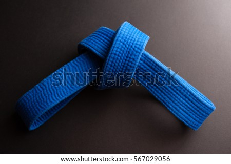 Blue judo belt tied in a knot isolated on black background Royalty-Free Stock Photo #567029056