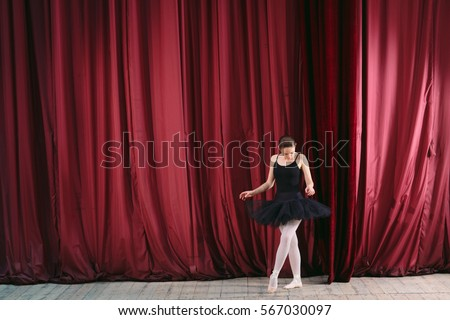 Young ballerina in black dress trains behind the scenes. #567030097