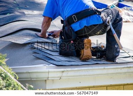 repairing the roof of a home; A worker replaces shingles on the roof of a home Royalty-Free Stock Photo #567047149