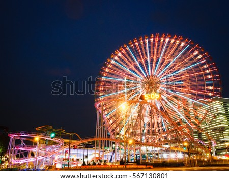 Amusement park at night - Ferris wheel and roller coaster Royalty-Free Stock Photo #567130801