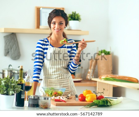 Young woman eating fresh salad in modern kitchen #567142789