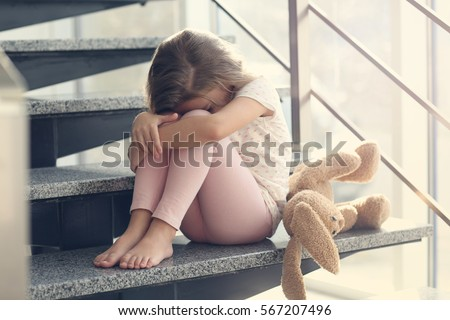 Sad little girl sitting on stairs Royalty-Free Stock Photo #567207496
