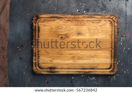 Empty cutting board with cloth napkin on a stone dark surface, top view #567236842
