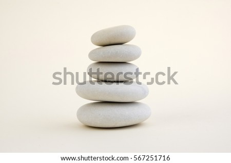 Harmony and balance, cairns, simple poise stones on white background, rock zen sculpture, five white pebbles, single tower, simplicity #567251716