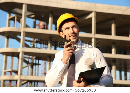 Handsome engineer with portable radio transmitter and clipboard standing against unfinished building #567285958