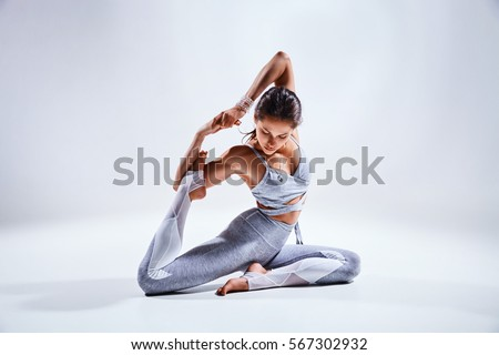 Sporty young woman doing yoga practice isolated on white background - concept of healthy life and natural balance between body and mental development Royalty-Free Stock Photo #567302932