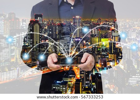 Double exposure of connectivity concept - businessman using smartphone with city overlay #567333253
