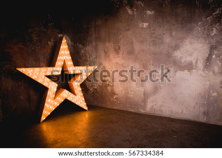 Large wooden star with a large number of lights are lit. Beautiful decor, design. Loft style Studio. Dark concrete background. Christmas, holiday, honorary star. Five stars 5 stars #567334384