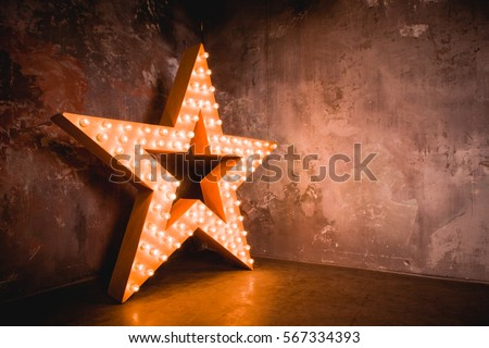 Large wooden star with a large number of lights are lit. Beautiful decor, design. Loft style Studio. Dark concrete background. Christmas, holiday, honorary star. Five stars 5 stars #567334393