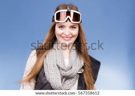 Woman skier girl wearing warm clothing ski googles portrait. Winter sport activity. Beautiful sportswoman on blue studio shot #567358612
