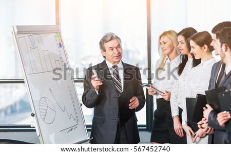 Head of business team explains to his colleagues the methods  sales growth, using a stand with charts and diagrams Royalty-Free Stock Photo #567452740