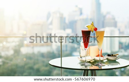 Cocktail glasses on table in rooftop bar against city view, Romantic dating anniversary, Beautiful rooftop bar in Bangkok. #567606970