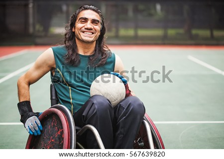 handsome determined disabled rugby player in a wheelchair on a stadium  #567639820