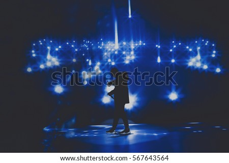 Rap & trap & hip hop star / singer perform on stage of nightclub in front of bright screen with stars. Music hall performing arts event. Dark background, smoke, concert  spotlights #567643564