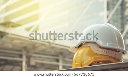 white, yellow hard safety helmet hat for safety project of workman as engineer or worker, on concrete floor on city Royalty-Free Stock Photo #567718675