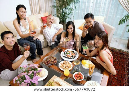 Adults sitting in living room, having a party, smiling at camera #567743092