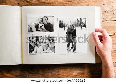 Hand holding photo album with pictures of senior couple. Studio  Royalty-Free Stock Photo #567766621