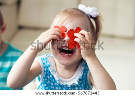 the girl 3 - 4 year closed her eyes red paper cut outs flowers standing next to the boy and stares at the baby