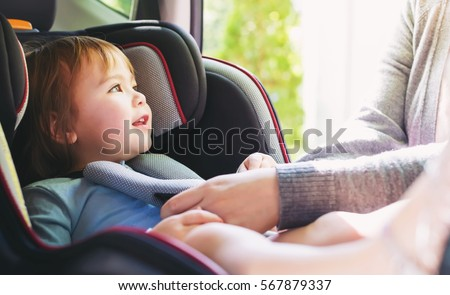 Toddler girl buckled into her car seat Royalty-Free Stock Photo #567879337