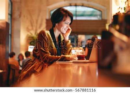 Caucasian female is typing emails on the laptop to the friends while having rest in a cafe. Beautiful woman is surfing the web on a portable computer while relaxing with a cup of tea.  #567881116