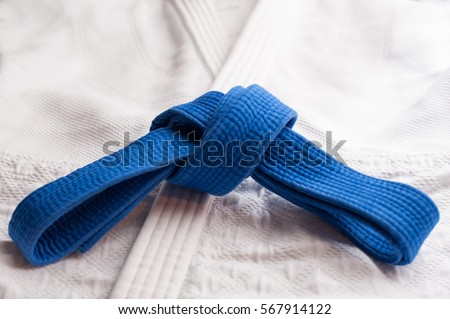 Blue judo, aikido or karate belt tied in a knot with white kimono in background Royalty-Free Stock Photo #567914122