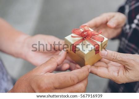 Senior man hand give a gift box to senior woman hand #567916939