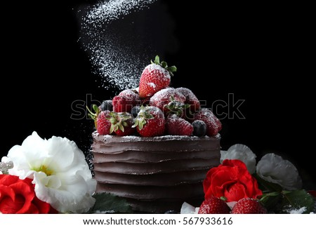 Chocolate cake with strawberry and raspberry decorating with flowers on black background #567933616