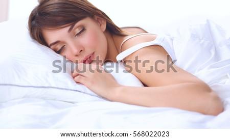 Beautiful girl sleeps in the bedroom, lying on bed #568022023