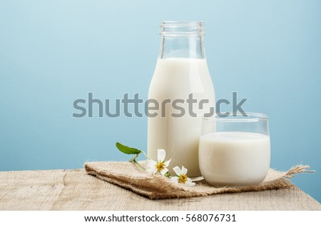 A bottle of milk and glass of milk on a wooden table on a blue background Royalty-Free Stock Photo #568076731