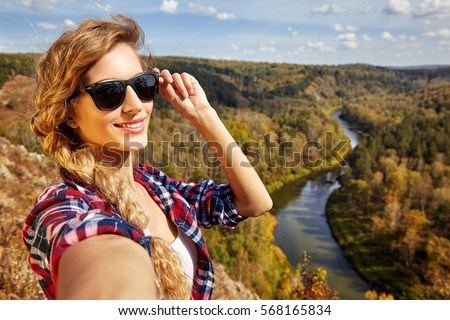 Young blonde smiling, woman tourist  on a cliff taking selfie picture on background of autumn landscape with the river Berd. Russia, Siberia, Salair
