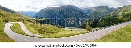Road through the grassy hills. Mountain road. Cloudy summer day. Travel by car. #568190584