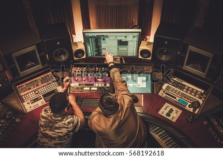 Sound engineer and musician recording song in boutique recording studio. #568192618