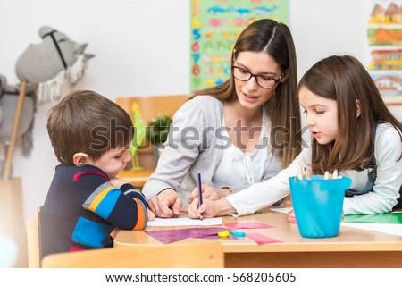 Teacher Working with Children in Preschool Classroom