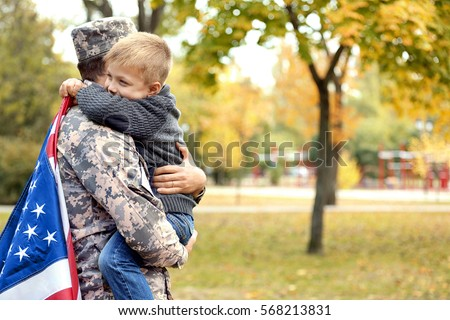 Soldier reunited with his family on a sunny day Royalty-Free Stock Photo #568213831
