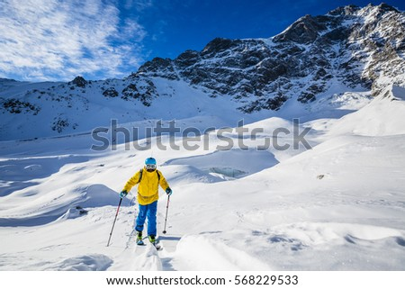 Mountaineer backcountry ski walking up along a snowy ridge with skis in the backpack. In background blue sky and shiny sun and Ortler in South Tirol, Italy.  Adventure winter extreme sport.  #568229533