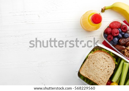 Healthy lunch boxes with sandwich, fresh vegetables, fruits and nuts on white wooden background. From top view #568229560
