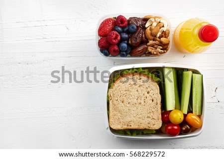 Healthy lunch boxes with sandwich, fresh vegetables, fruits and nuts on white wooden background. From top view #568229572