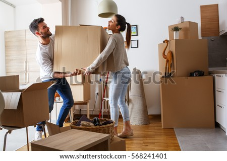 Young couple carrying big cardboard box at new home.Moving house. Royalty-Free Stock Photo #568241401