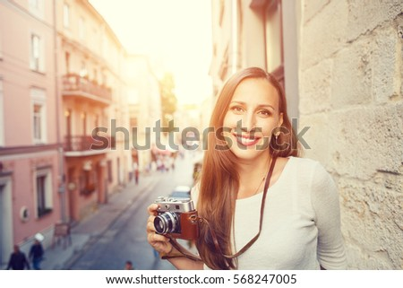 Young cheerful woman standing with camera at the balcony in european town #568247005