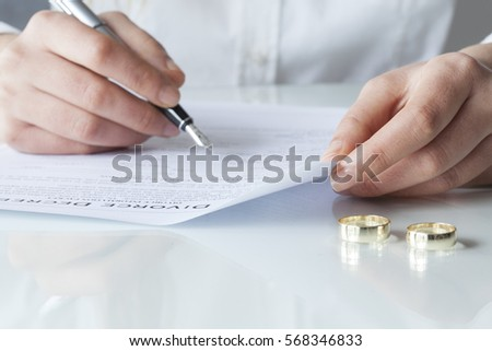 Wife signs divorce decree form with ring #568346833