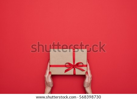 Top view of female hands holding present box package in the palms isolated over flat lay background  Royalty-Free Stock Photo #568398730