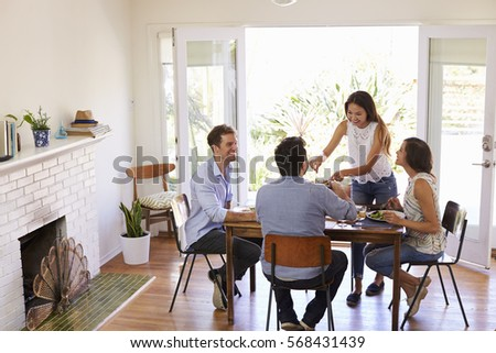 Group Of Friends Enjoying Dinner Party At Home Together #568431439