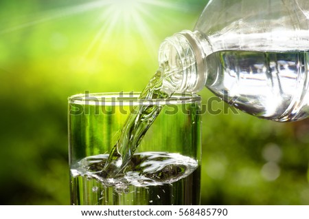 Drink water pouring in to glass over sunlight and natural green background  Royalty-Free Stock Photo #568485790