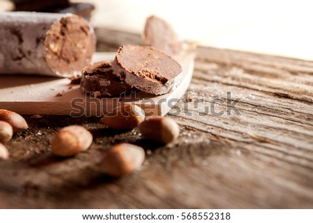 Cuts of chocolate sausage with hazelnuts on wooden background #568552318