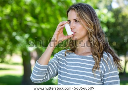 Woman using asthma inhaler in a park Royalty-Free Stock Photo #568568509