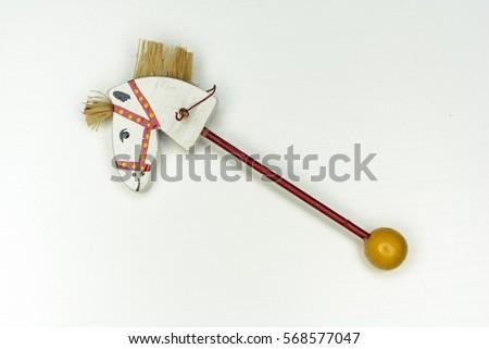 white wood horse head on stick vintage toy isolated on white background